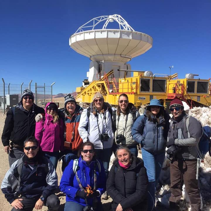Ten people in coats with cameras posing in front of large radio telescope pointed straight up.