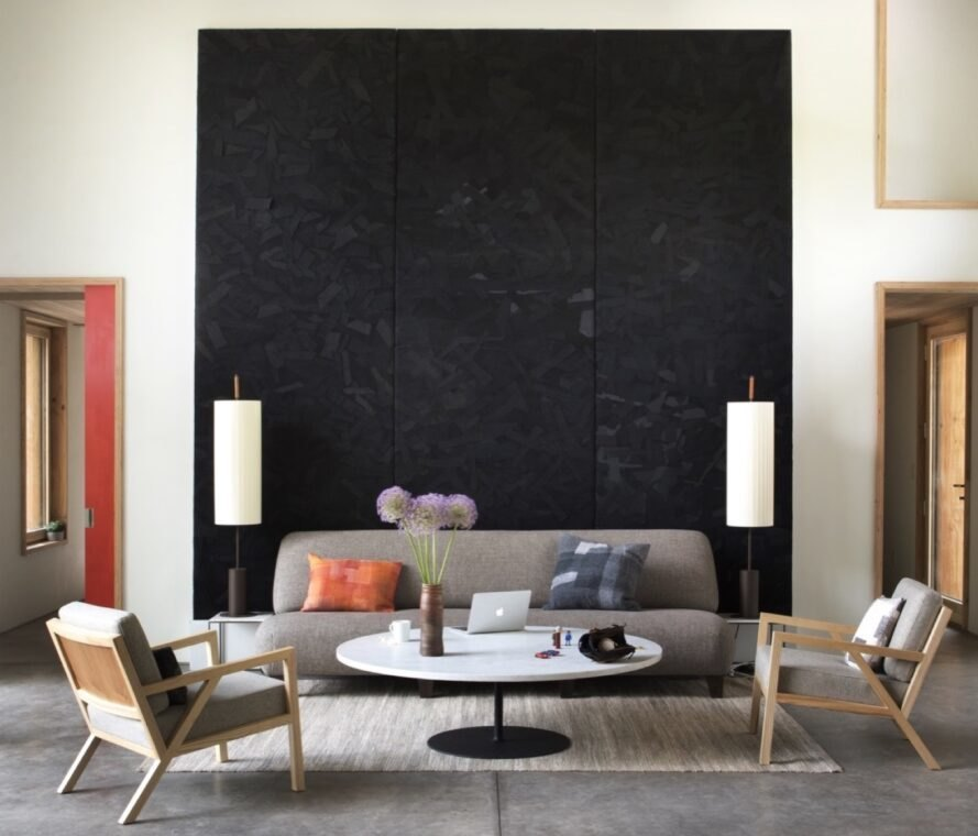 beige sofa and chairs in front of black wall art