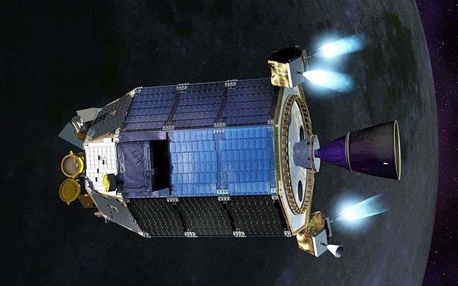 Blue cylindrical spacecraft with small rockets firing, moon in background.