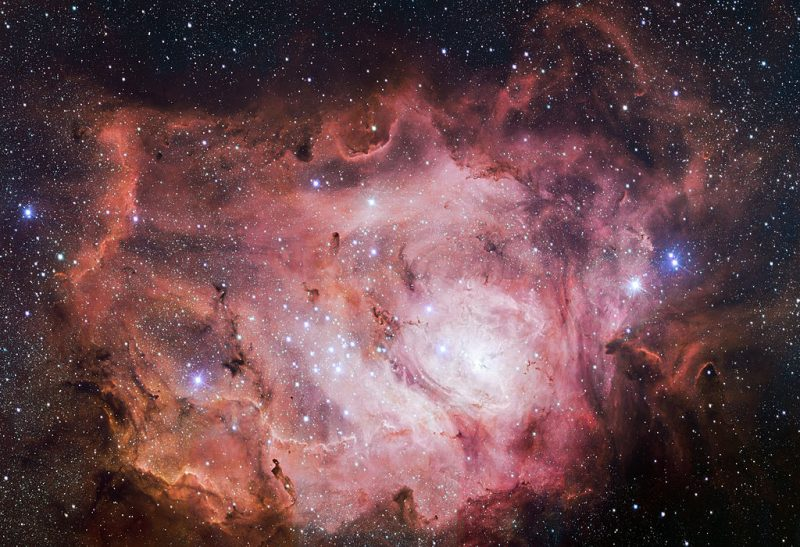 A celestial cloud of swirling gases, concentric pink ruffles containing patch of very bright stars.