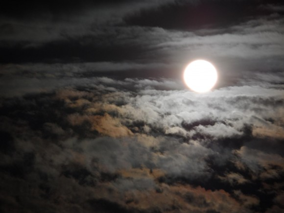 Full moon above puffy moonlit clouds.