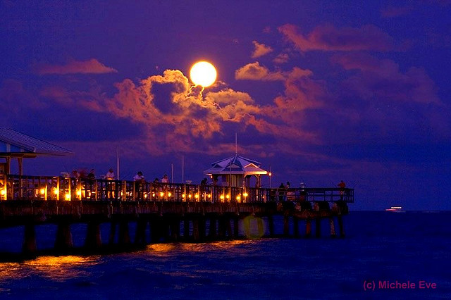 Full moon with glowing orange moonlit clouds against cobalt sky over a long, lighted pier.