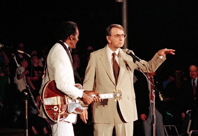 White-suited man with guitar next to gesturing man in tan suit, microphone in front of the pair.