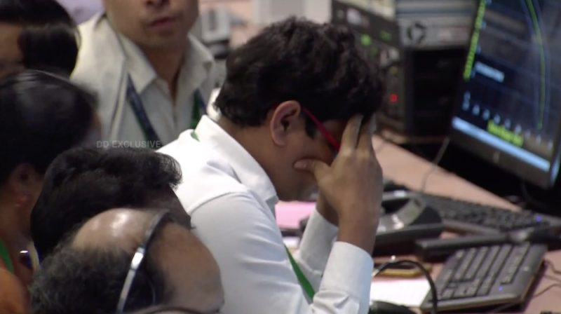 A man at a computer terminal with his head in his hands.