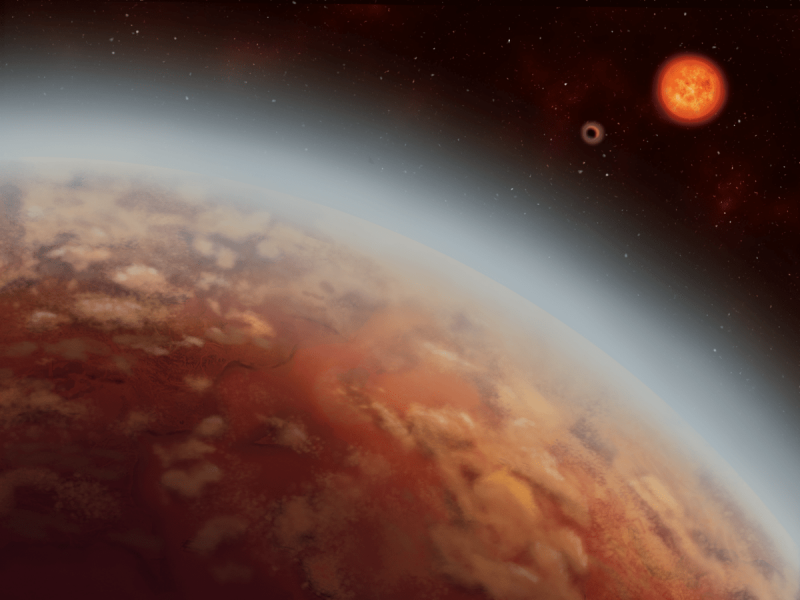 Patchy reddish planet with hazy atmosphere orbiting a red dwarf star.