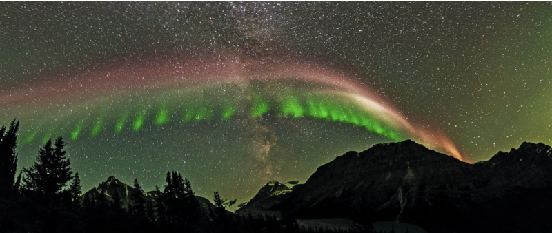 A vast, multicolored arc set against a background of northern lights.