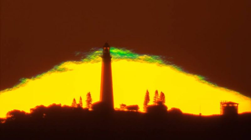 Lighthouse silhouetted against yellow partial sun topped with bright green.