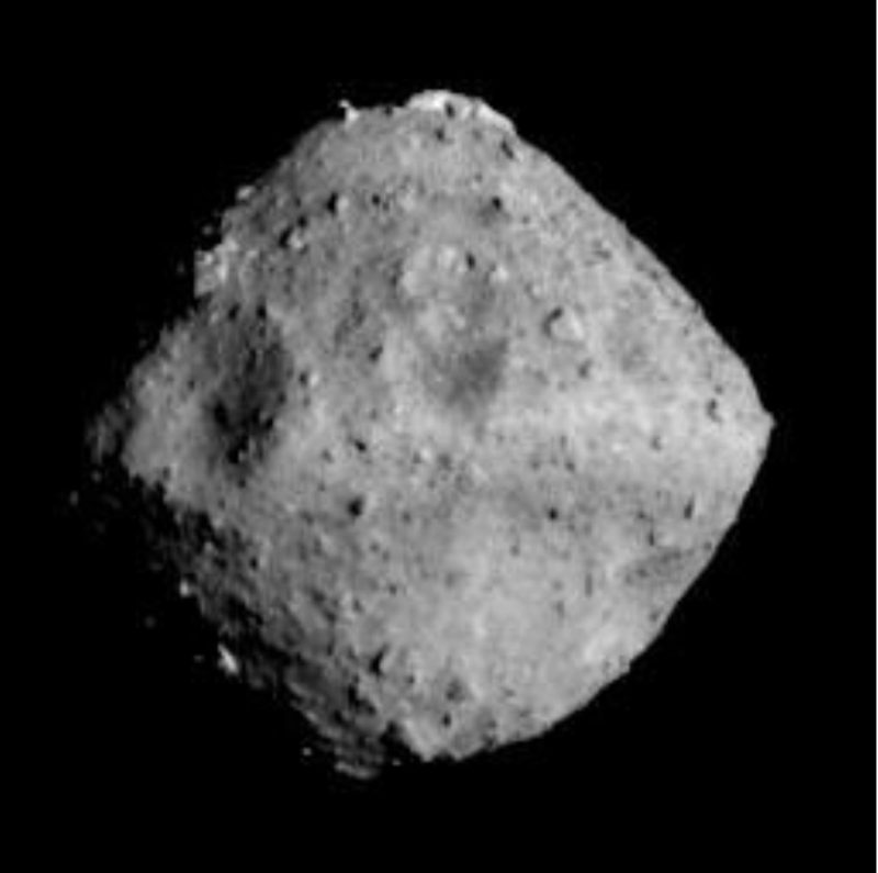 A blocky gray asteroid, shaped somewhat like a spinning top, with rough rocky surface.