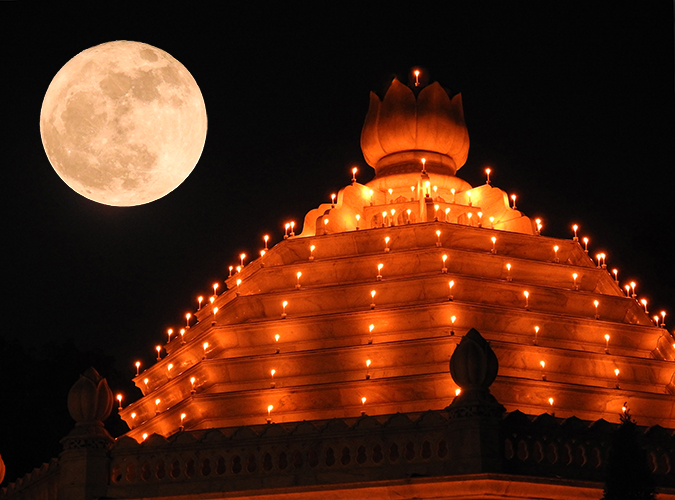 Giant yellow full moon over multi-story temple with candles around every floor and onion dome on top.