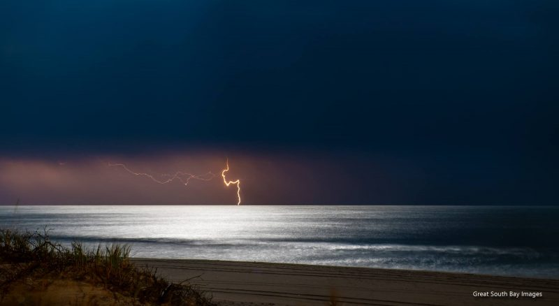 Distant lightning bolt from cloudy sky above silvery ocean.