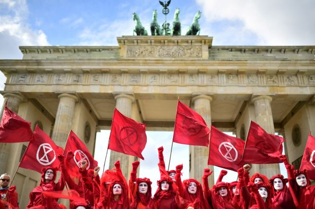 """FORETELLING OF THE APOCALYPSE: Red Rebel Brigade activists, part of the Extinction Rebellion global movement, perform in front of the Brandenburg Gate in Berlin, Germany. The climate-crisis movement has planned a """"spring rebellion"""" this week, including marches aimed at blocking traffic in major cities. Photograph: Clements Bilan/EPA"""