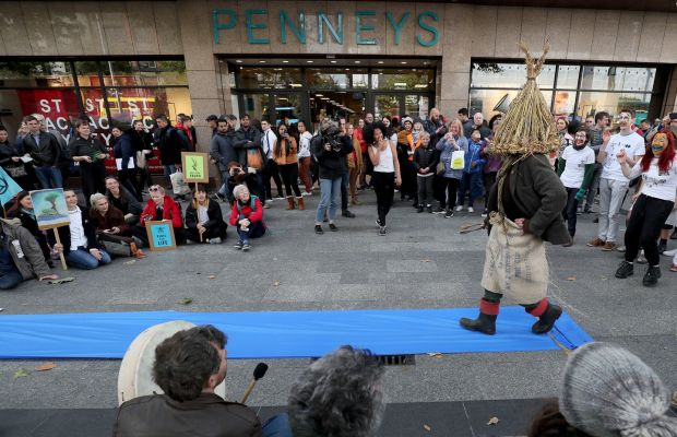 """REBELLION NOW THE FASHION? Protesters dressed as wren boys perform an impromptu """"fashion show"""" outside Penneys on O'Connell Street in Dublin during an Extinction Rebellion (XR) demonstration. Fashion retailers have come under intense scrutiny in the last year from environmental activists. Photograph: Brian Lawless/PA Wire"""