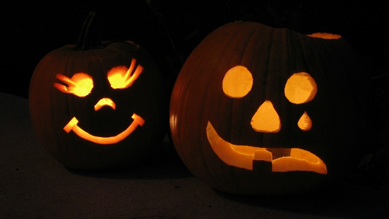 Two pumpkins with lights glowing through faces cut in them.