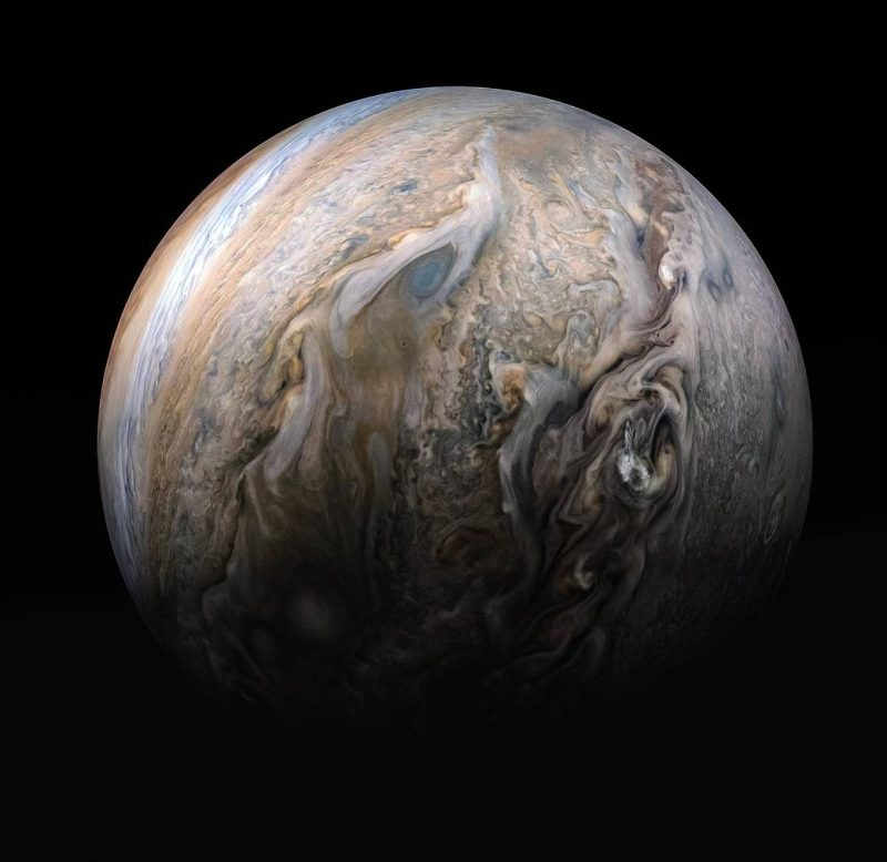 Nearly full Jupiter, showing colorful, wavy-edged, spiraling bands.