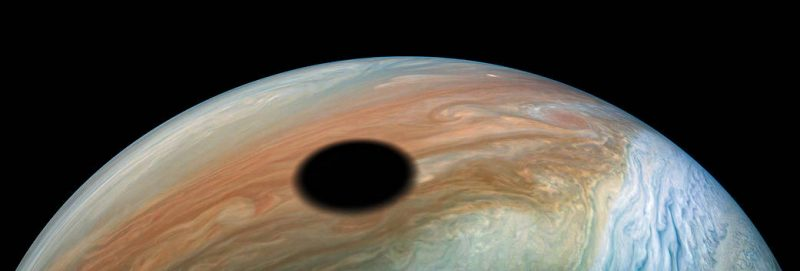A large, round, black shadow on Jupiter's colorful banded clouds.
