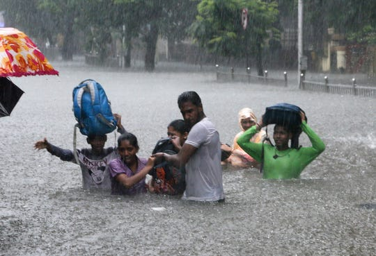 In this Sept. 4, 2019, file photo, people hold hands and navigate their way through a flooded street as it rains in Mumbai, India. The number of people threatened by climate change-triggered flooding is about three times higher than previously thought, a new study says. But it's not because of more water. It's because the land, especially in Asia and the developing world, is several feet lower than what had been calculated.