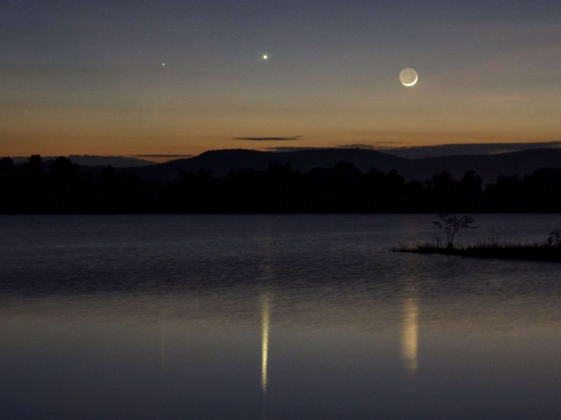 A trio of objects at twilight, whose reflection shines in a lake: fainter Mercury, brighter Venus and a very thin waxing crescent moon.