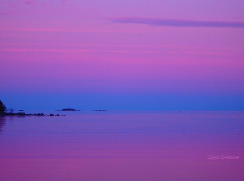 Purplish pink sky over blue band above horizon, reflected in calm sea.