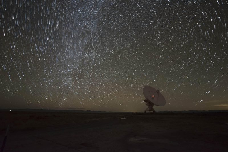 Distant, single dish-shaped antenna and circular star trails.