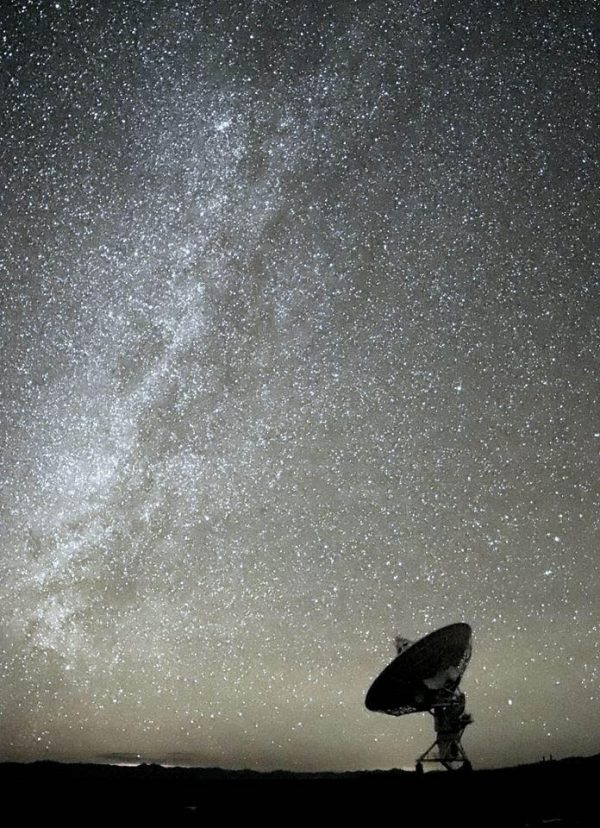 Dish-shaped antenna silhouetted against Milky Way.