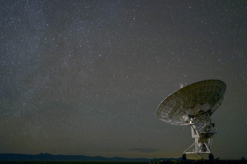 Dish-shaped antenna against background of a starry sky.