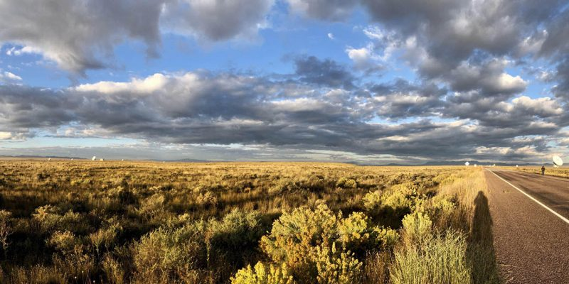 Flat yellow-brown fields under a blue sky with clouds, straight road.