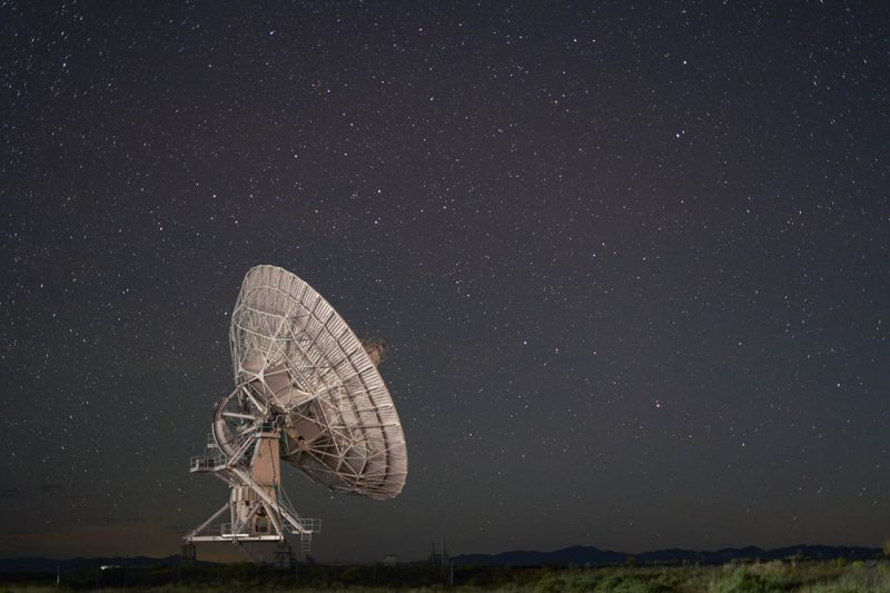 White bowl-shaped radiotelescope pointing up at starry night sky.