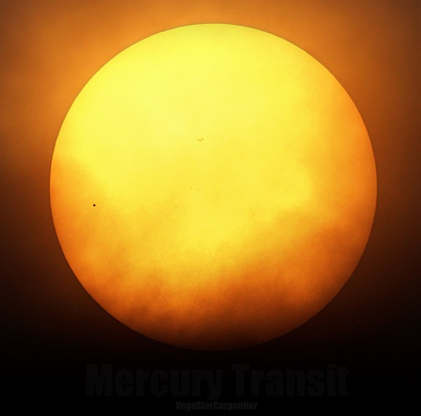 Large yellow sun with tiny black dot on it.
