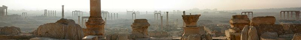Misty scene with very many ancient columns standing without roofs or walls.