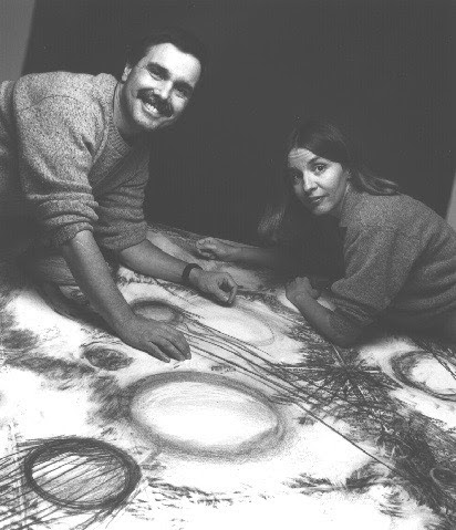 A man and a woman leaning over a table covered with a cosmic-looking graphic.