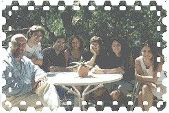 A group of people sitting outside, around a round table.