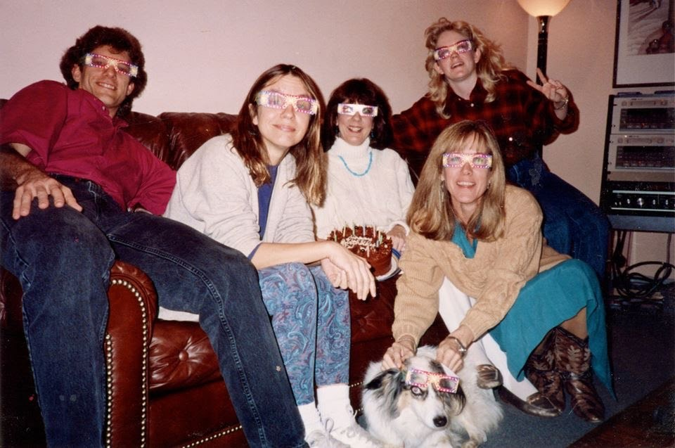 Five people and a dog, with big funny glasses on, lounging on a couch.