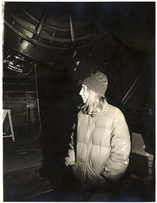 A young woman in a puffy jacket and sock hat, standing next to the base of a large telescope.