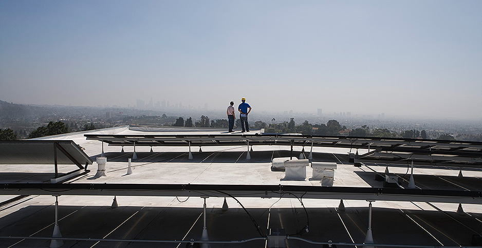 Workers inspect a solar array in Los Angeles. Photo credit: West Coast Surfer/picture alliance / moodboard/Newscom