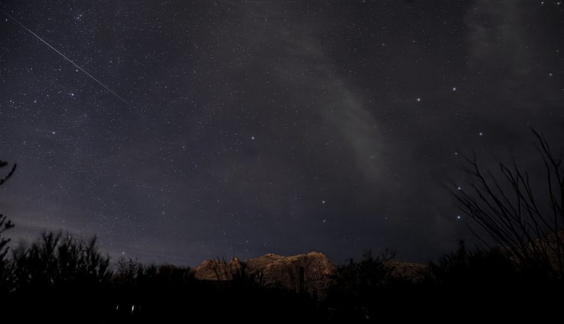 Bright meteor streaking through sky, near the arc in the Big Dipper's handle.