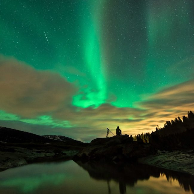 Silhouetted man with camera tripod watching thin streak in sky against giant, swirly green aurora.
