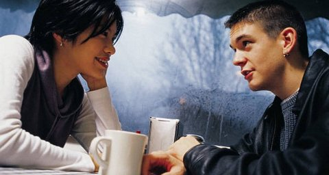 Young man and woman gazing into each other's eyes across a table with coffee cups on it.