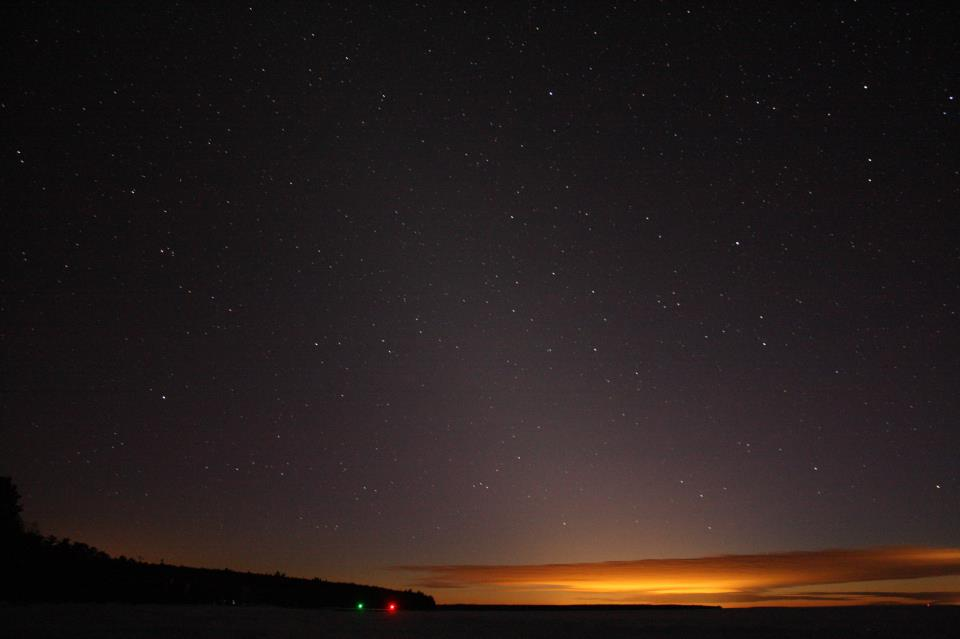 Zodiacal light extending up into star field with orange dawn light on the horizon.