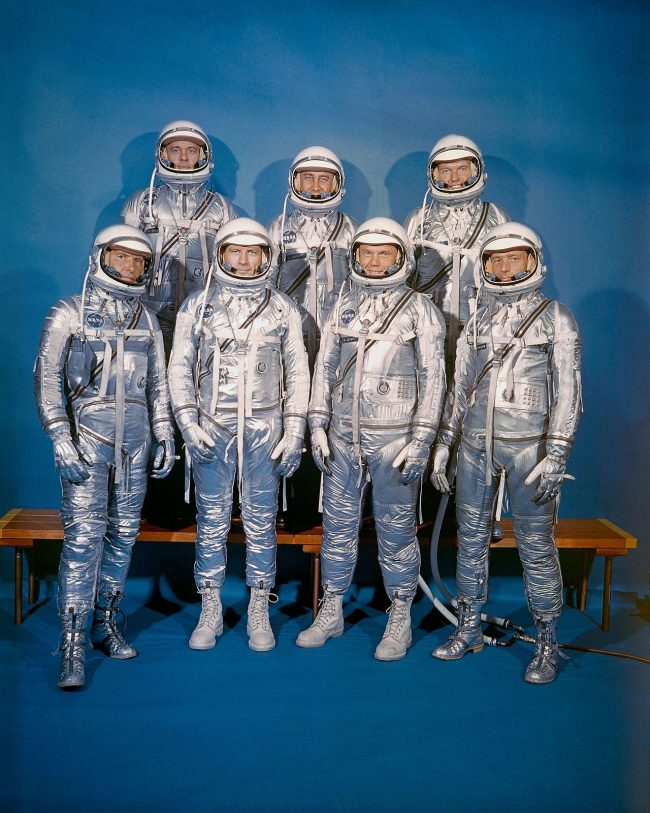 Group portrait of seven men in old-timey silver spacesuits.