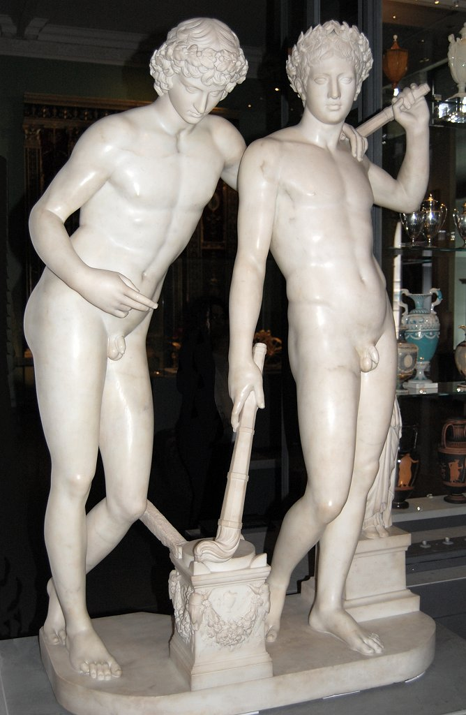 Marble statue of two nude young men, one with a laurel wreath on his curly hair.