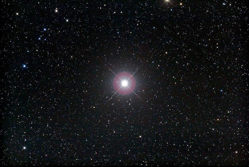 Image of bright star Pollux against a backdrop of many fainter stars.