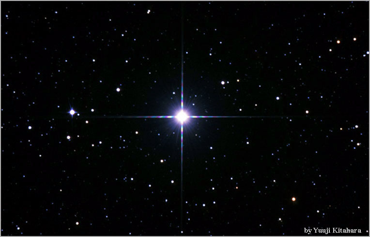 Very bright star in the middle of a black field of stars.