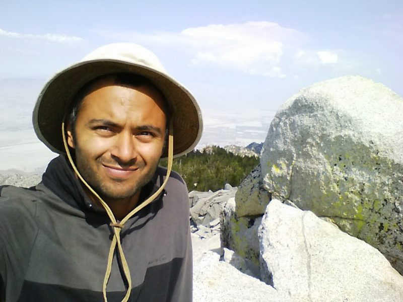 Smiling man in hat with boulder behind him.