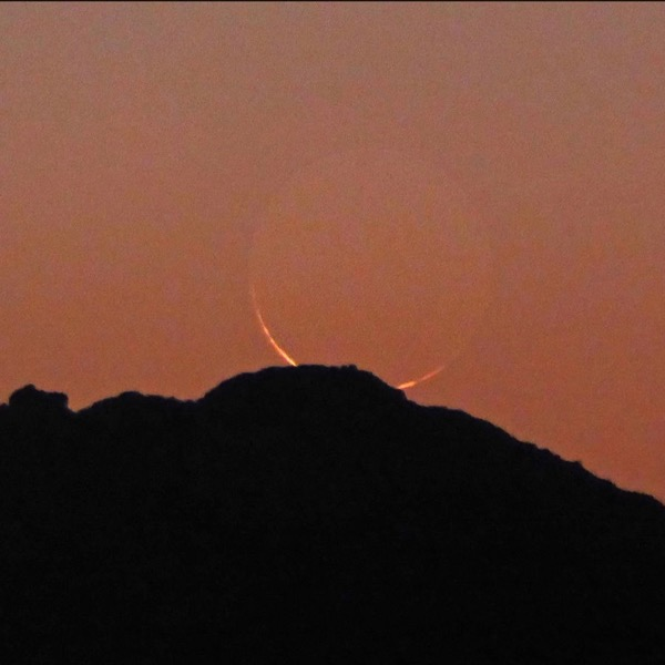 Very young moon - a thin crescent - setting behind a ridgeline, in a twilight sky.