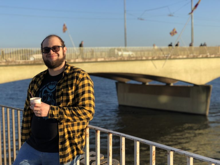 Smiling man with beard and sunglasses, with bridge in background.