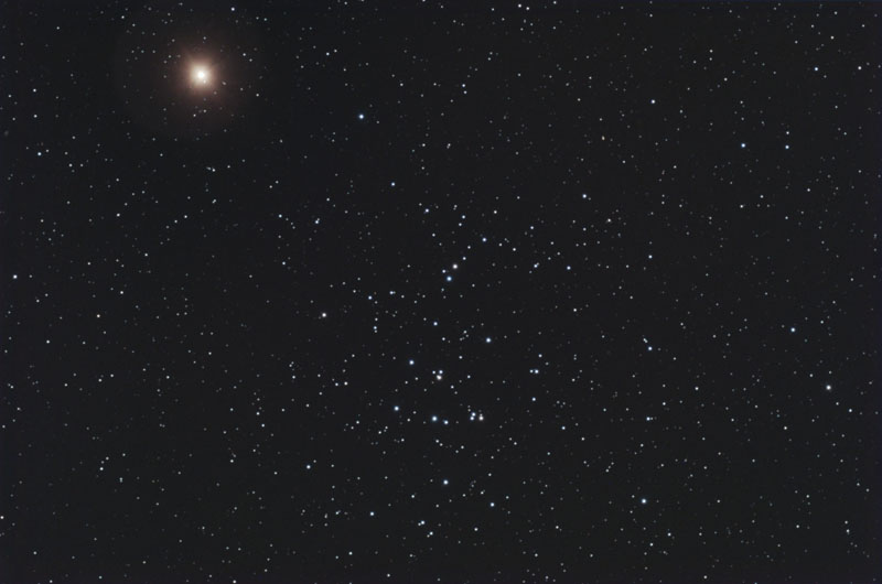 Star field with patch of several bright stars and fuzzy red dot near them.