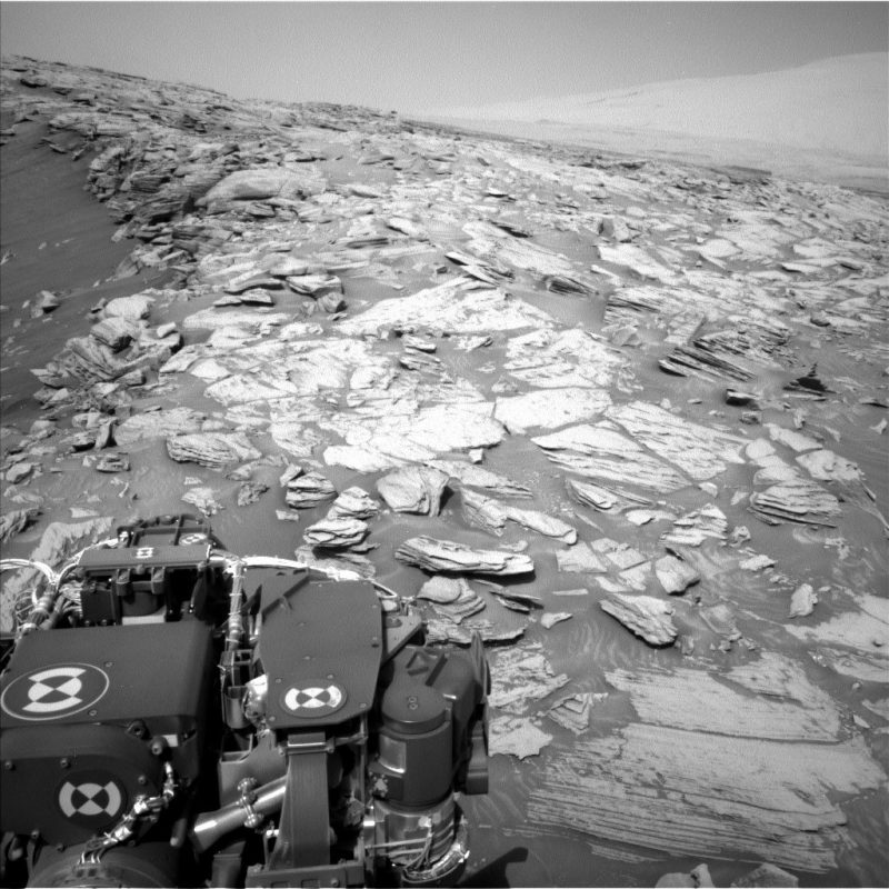 Gray rocky terrain with part of mechanical rover in foreground.