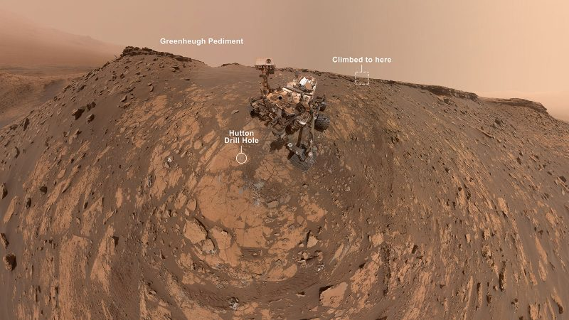 Mechanical rover in middle of brownish rocky landscape, with text annotations.