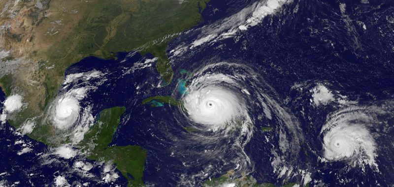 Orbital view of hurricanes: three giant white spirals on blue background with green land area to left.