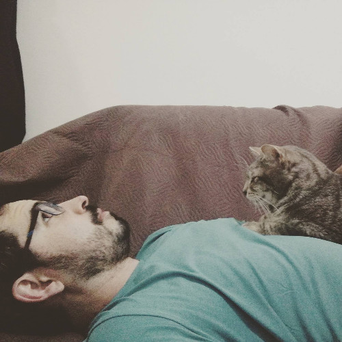 Bearded man in a green shirt lying on sofa with cat on his chest.